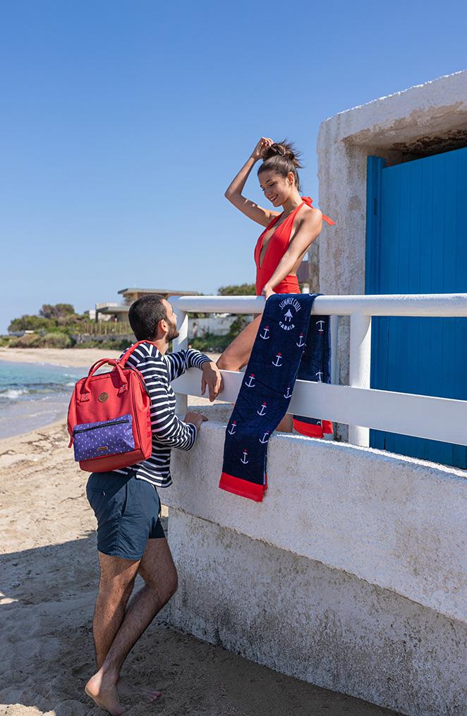 un homme et une femme se tiennent devant une cabine de plage à la porte bleue, l