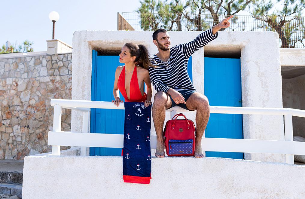 un homme et une femme se tiennent devant des cabines de plage aux portes bleues, l