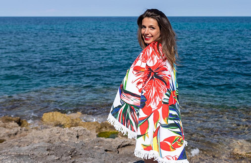 une jeune femme brune, enroulée dans une serviette de plage rouge avec des motifs à fleurs se tient devant l
