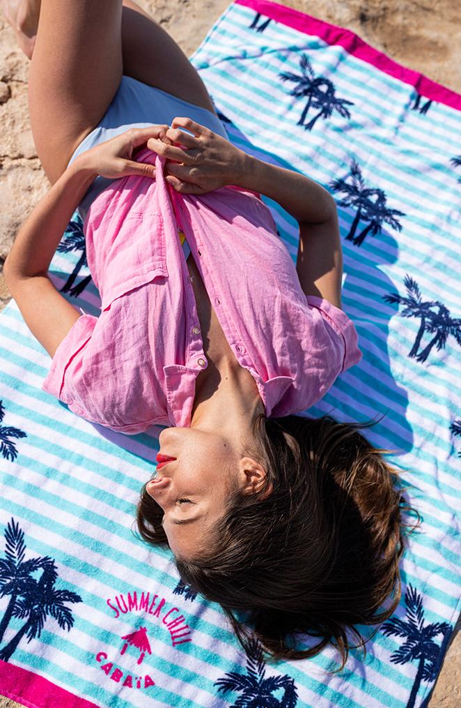 une jeune femme brune est étendue sur une drap de bain bleu ciel avec des motifs de palmiers bleu marine, elle porte une chemise rose et croise ses bras sur son ventre