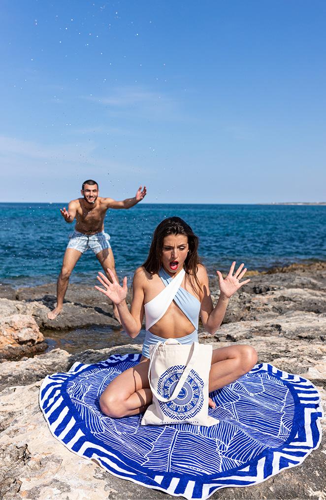 une jeune femme assise sur le bord de mer sur un drap de bain rond et bleu, tient devant elle un sac, elle se fait surprise par un homme derrière elle qui lui l