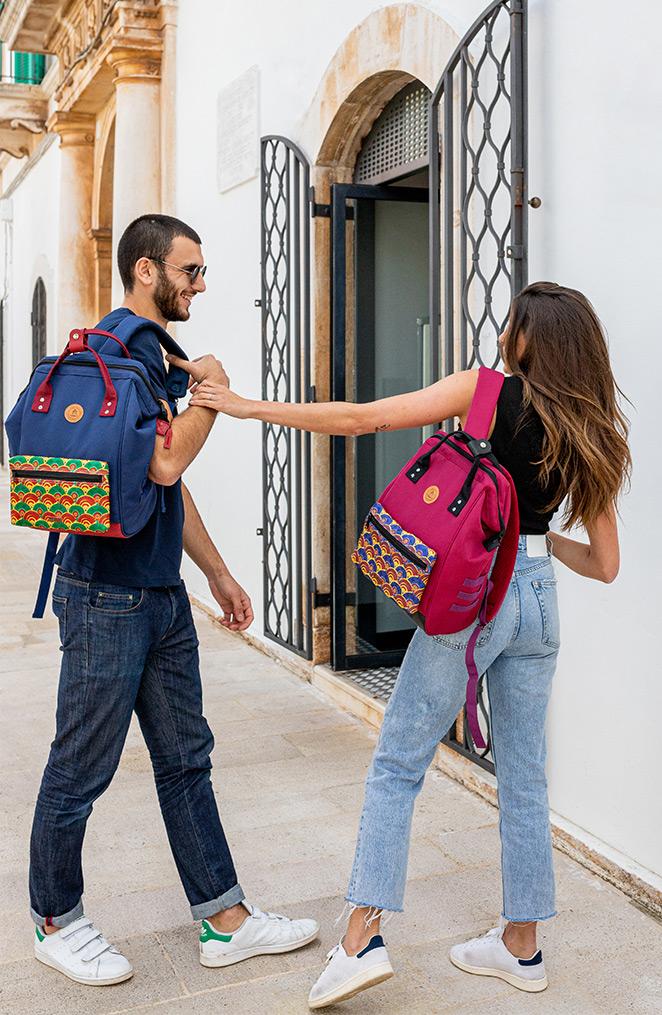 un homme et une femme joue dans la rue, ils portent tous les deux un sac-à-dos, le garçon à droite porte un sac bleu et la fille à droite un sac violet