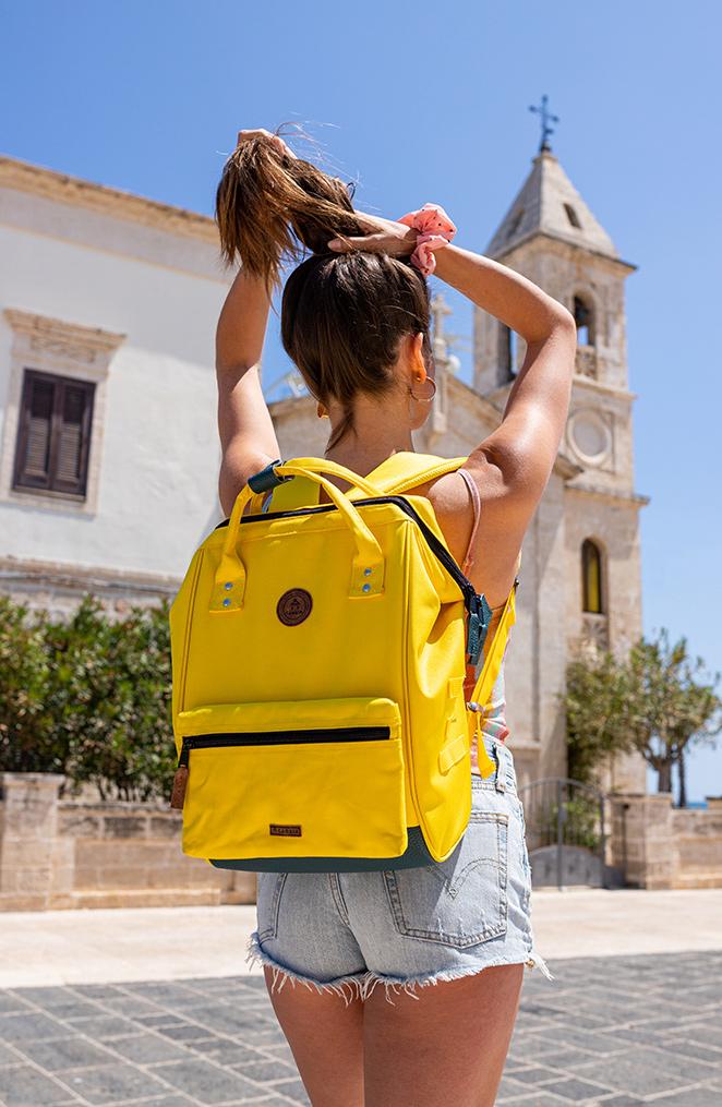 une jeune femme de dos devant une église italienne, portant un sac à dos jaune, se fait une queue de cheval