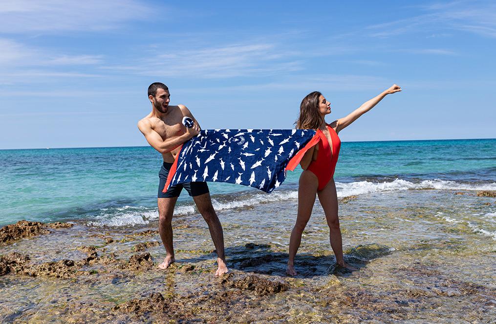 un homme et une femme jouent dans la mer avec une serviette de plage, qui joue le rôle de cap de superwoman à la mise en scène